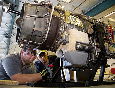 two men repairing aircraft engine