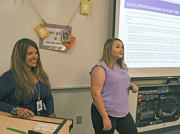female teacher and student presenting to class