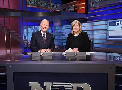 photo of two anchors sitting at a desk for the Nightly Business Report
