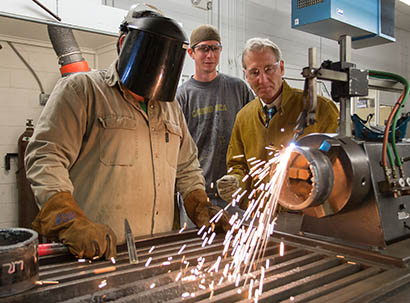 welding students and instructor with sparks