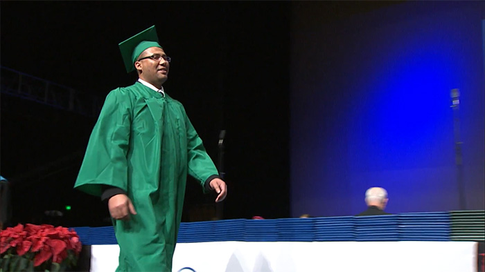 Graduate in green cap and gown