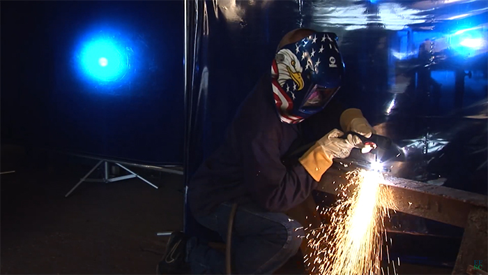 Welding with hooded welder and sparks