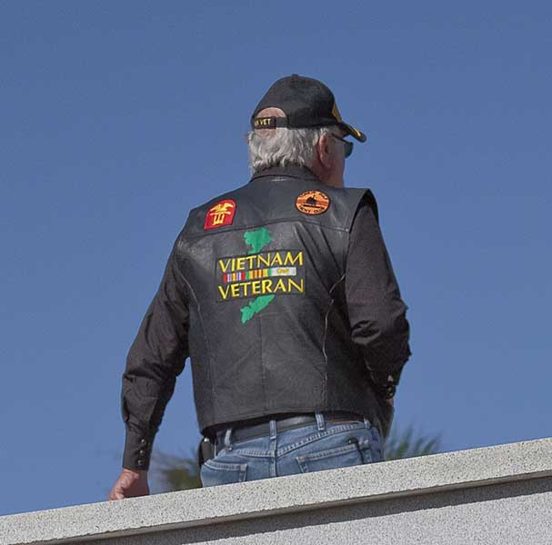 Man sitting on wall with vietnam veteran jacket