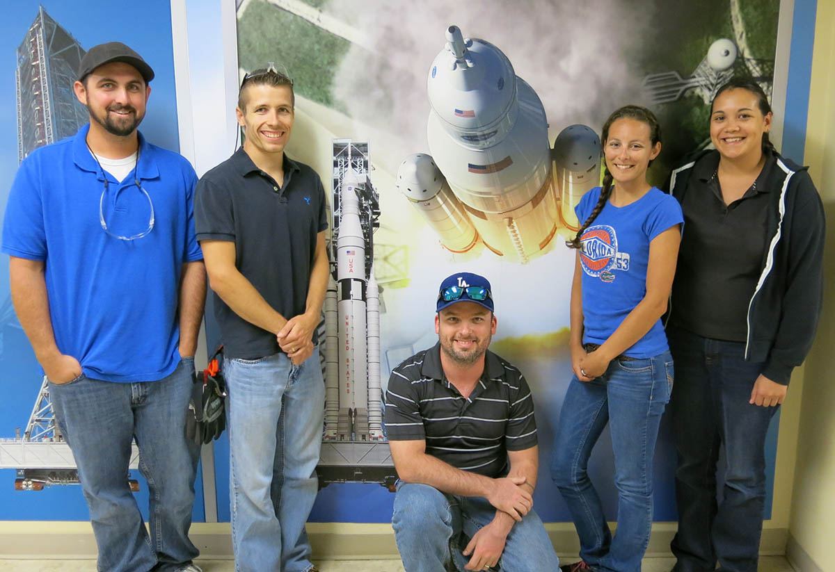 spacecraft and rocket images with five male and female students