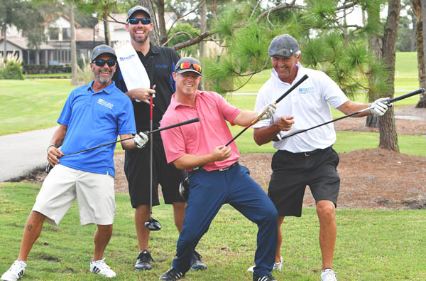four golfers playing clubs like guitars