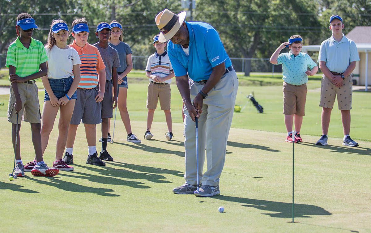 golf instructor with kids on putting green