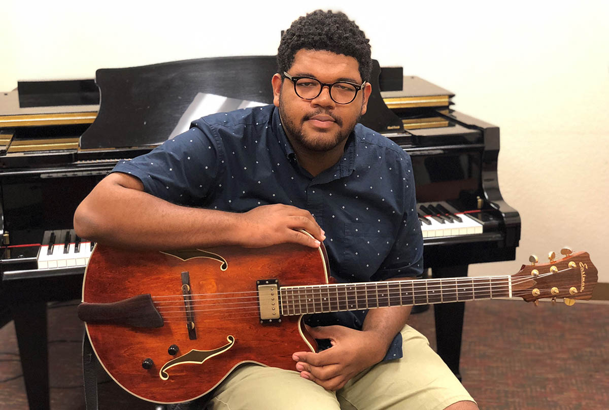 Ethan Bailey-Gould - EFSC music student with guitar in front of piano