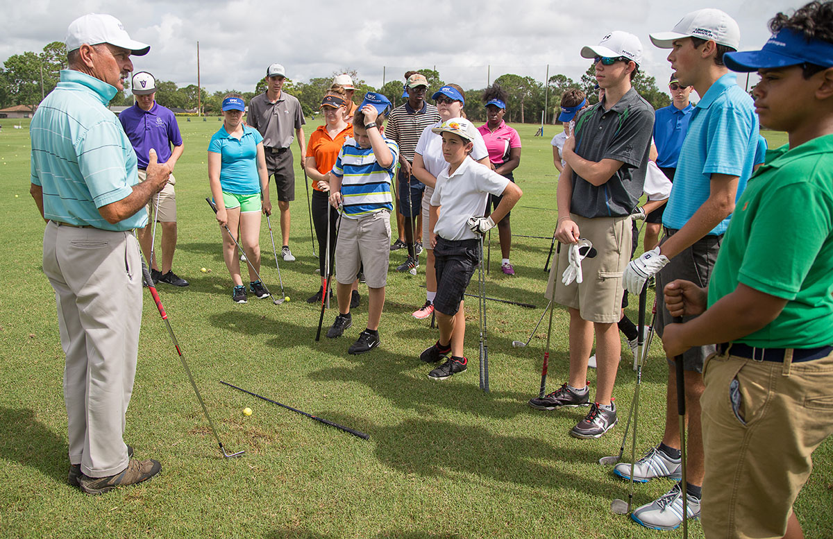 Golf Coach Jamie Howell instructing youth golf campers at outdoor driving range