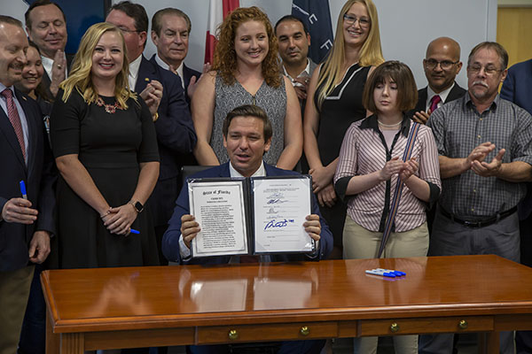 group of people with Florida Governor Rob DeSantis holding signed bill
