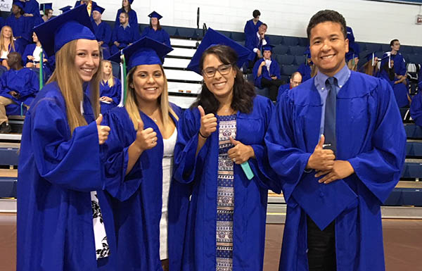 four graduates in blue robes