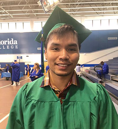 male graduate in green cap and gown