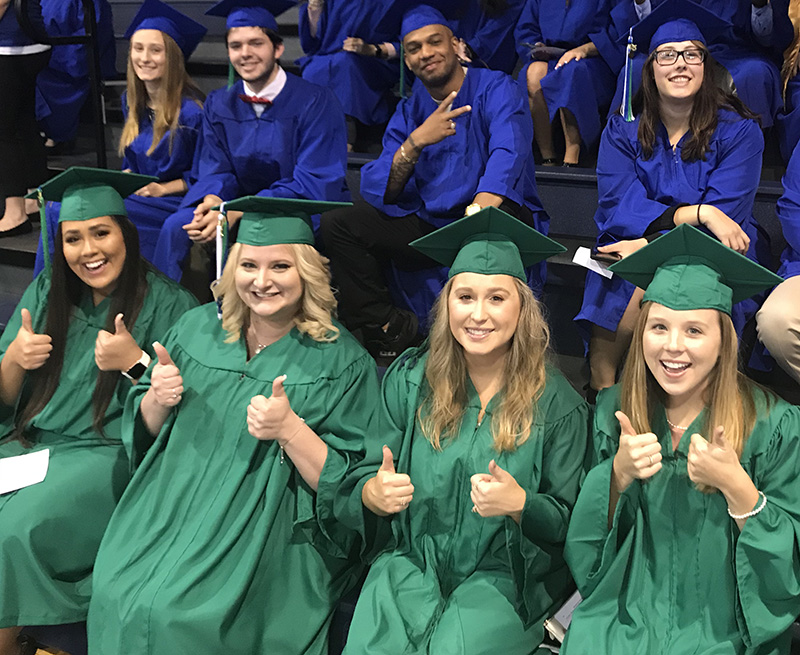 Group of graduates in green and blue robes
