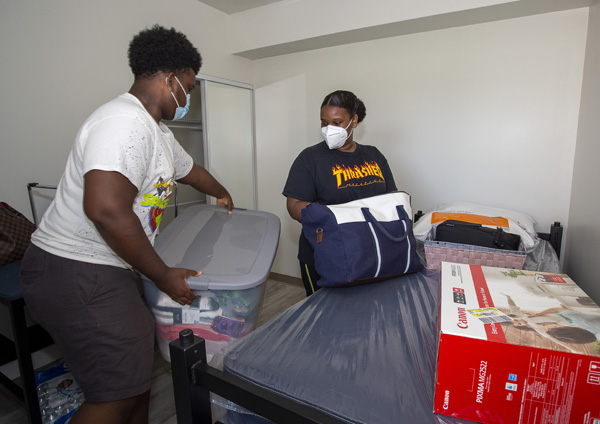 Mother and son unpack in student housing room at EFSC