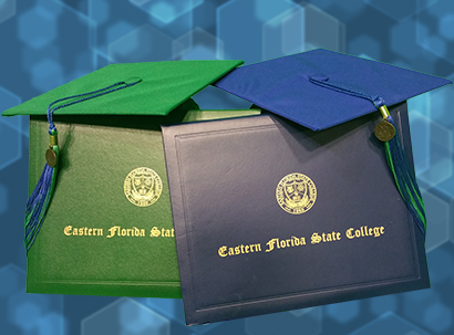 Two EFSC mortarboards, one green and one blue, sit atop two EFSC diploma covers with the same colors.