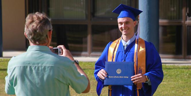 Father taking picture of student at graduation
